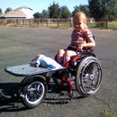Little girl in her FreeWheel Wheelchair Attachment with optional rack.
