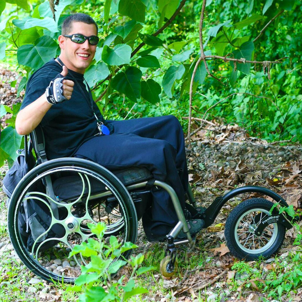 Young man traipsing through the woods in his FreeWheel Wheelchair Attachment.