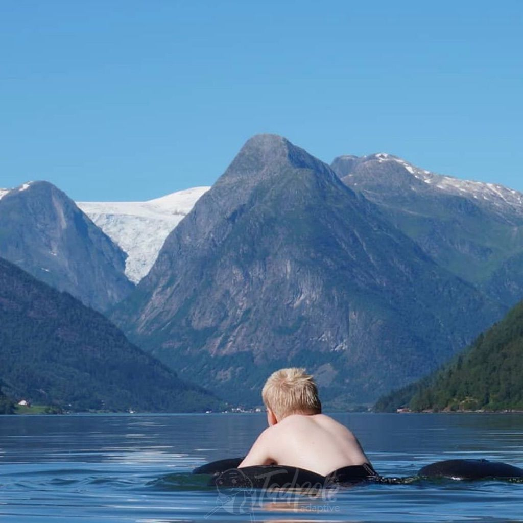 Boy in lake with mountain view in his Krabat special needs swimming aid.