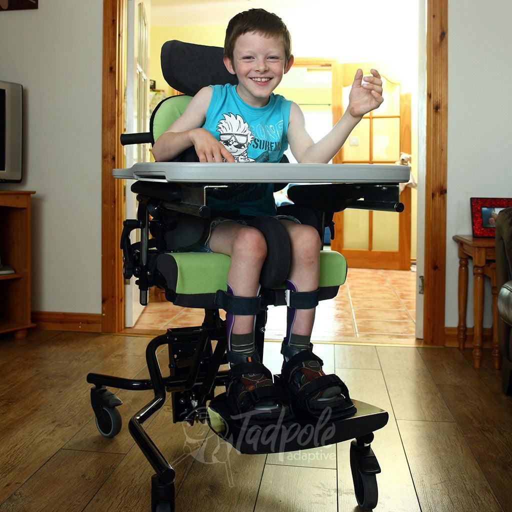 Young boy, at home, in his Green Leckey Everyday Activity Seat.