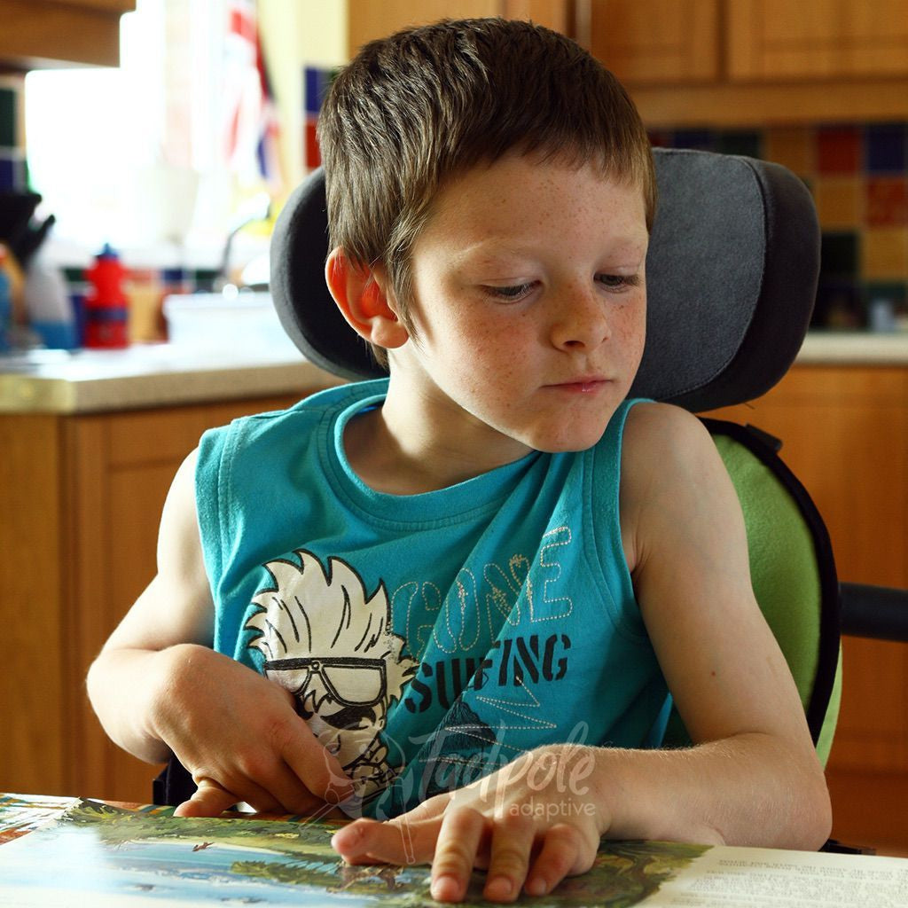 Boy in the kitchen, reading a book unattended in his Leckey Everyday Activity Seat.