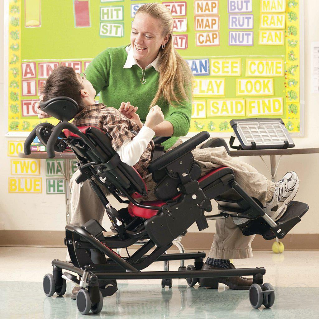 Little boy with teacher in his Rifton Large Activity Chair with Hi-Low Base.