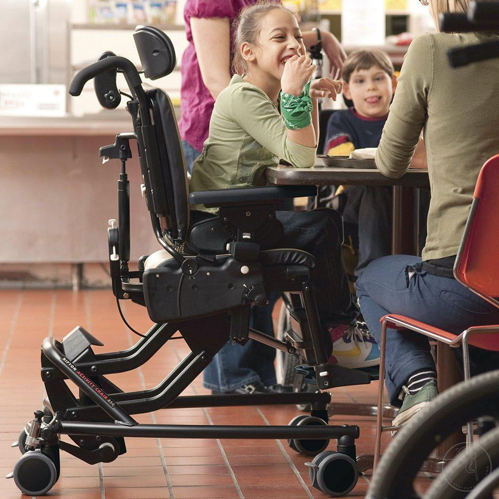 Girl in cafeteria with friends in her Medium Rifton Hi-Lo Activity Chair.