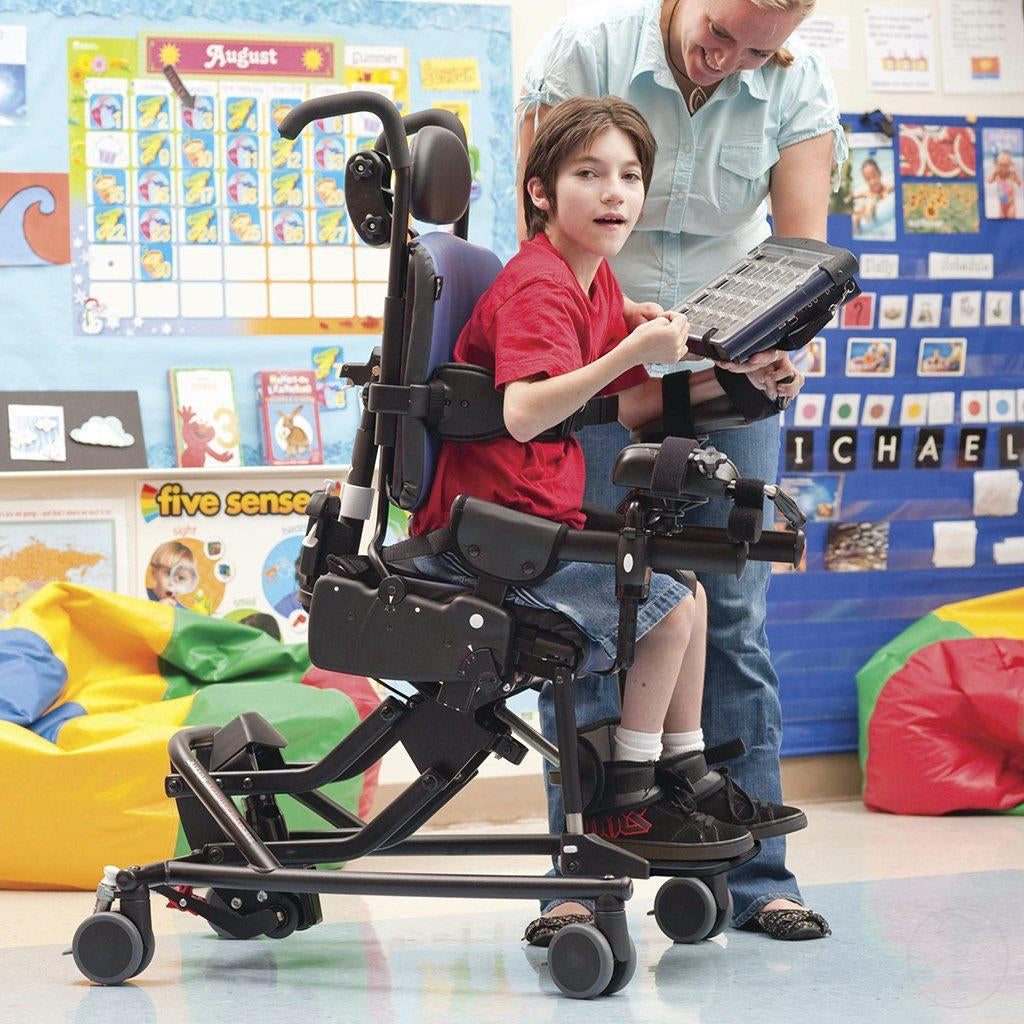 Boy tilting forward in classroom in his Medium Rifton Hi-Lo Activity Chair.