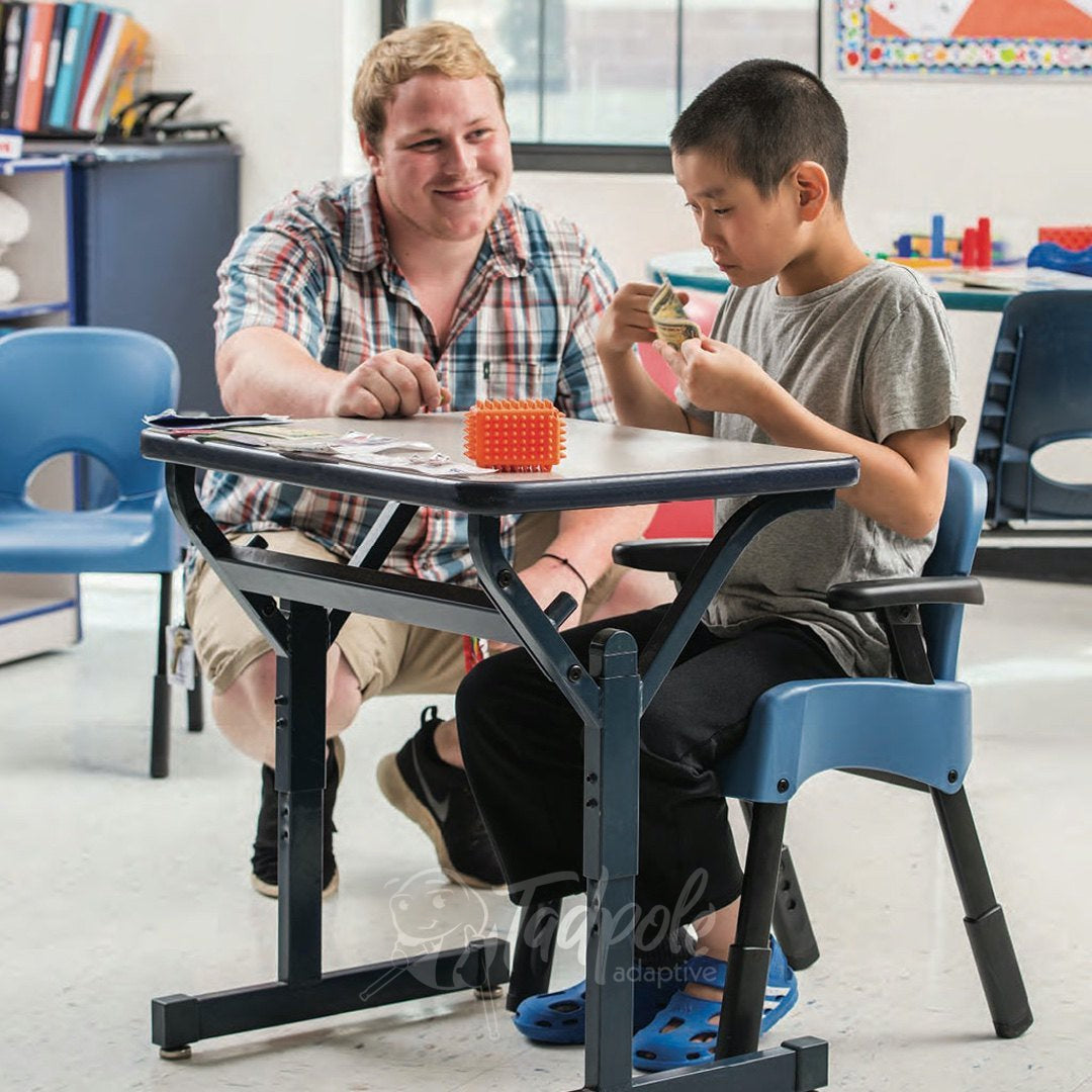 Boy participating in classroom activities with his teacher in the Rifton Compass Chair.