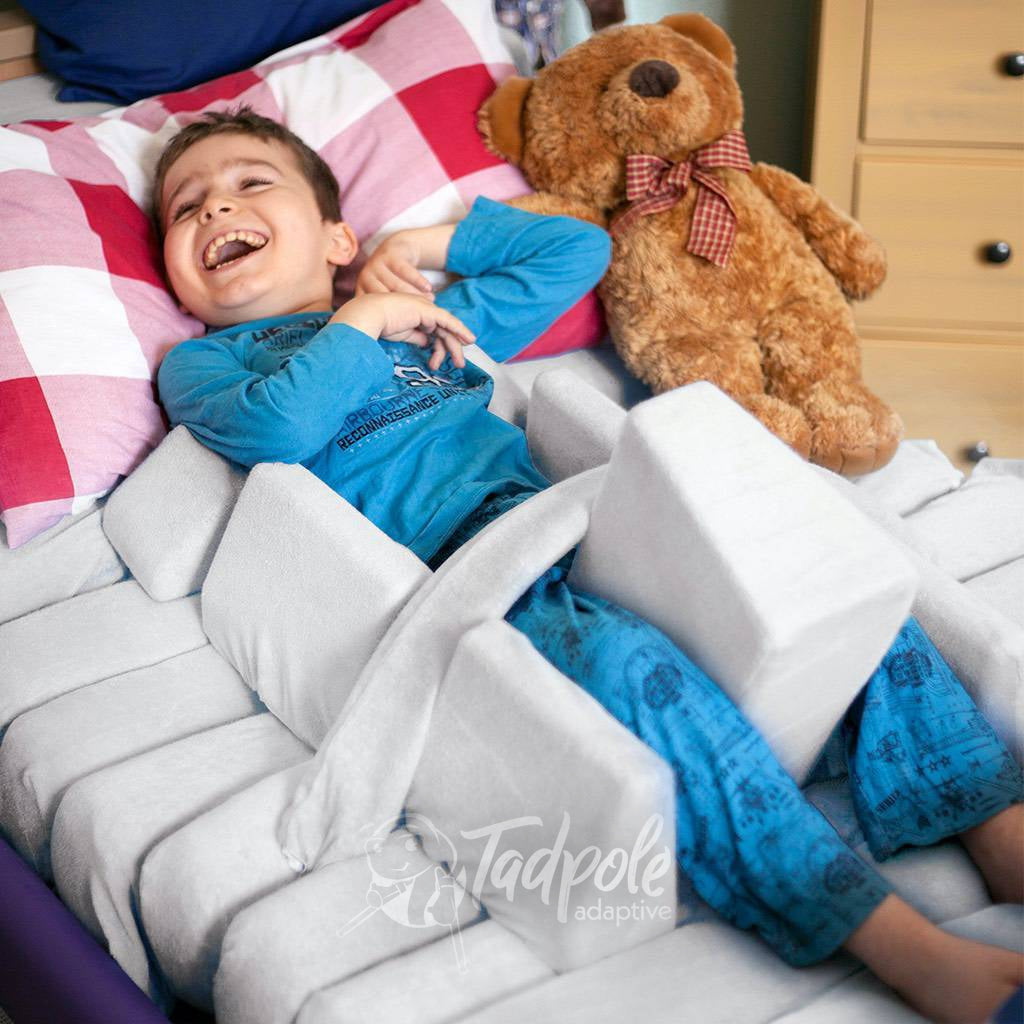 Young boy, on back in an adjustable bed using the Jenx Dreama - Postural Support Sleeping System.