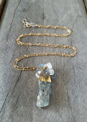 Clustered  necklace features a gold-dipped raw kyanite spear topped with a cluster of faceted labradorite and moonstone.