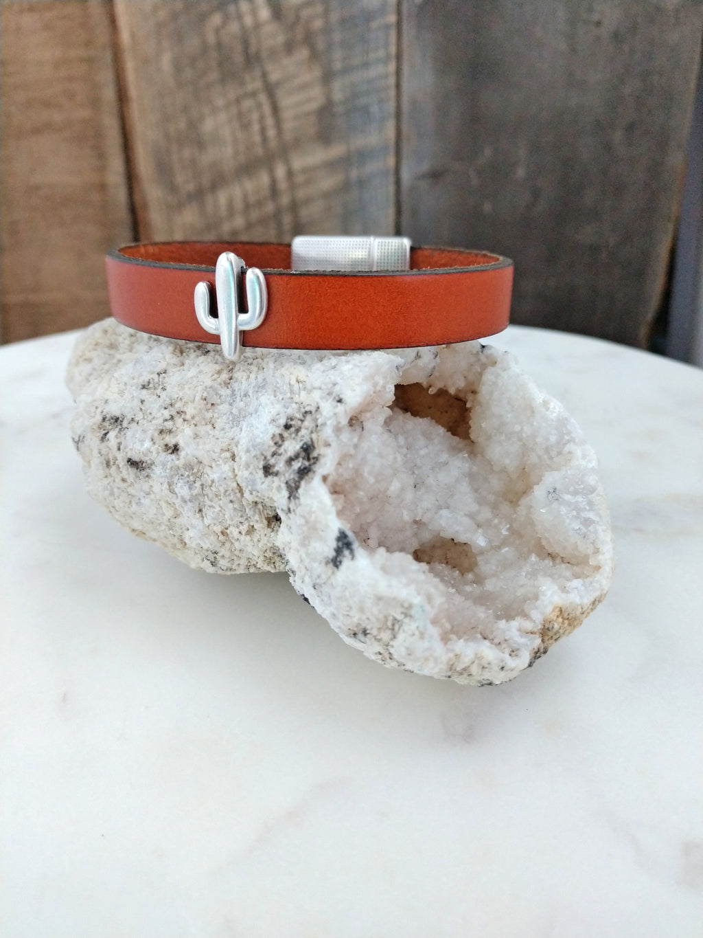 Burnt orange fine Italian leather is accented with a silver cactus. A southwestern inspired magnetic clasp secures the bracelet.