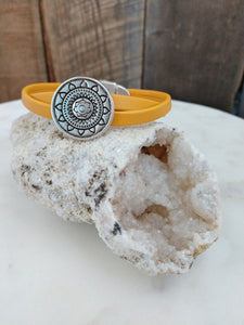 Two strips of mustard Mexican leather are twisted together with a silver sun mandala slider for a cool girl vibe. This bracelet is secured with a silver oval magnetic clasp.