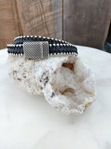 A long length of black leather edged with silver ball chain can be wrapped twice around the wrist or worn around the neck for a rocker chic look. This double wrap bracelet and/or choker length necklace stays secured with an oxidized, dotted magnetic clasp.