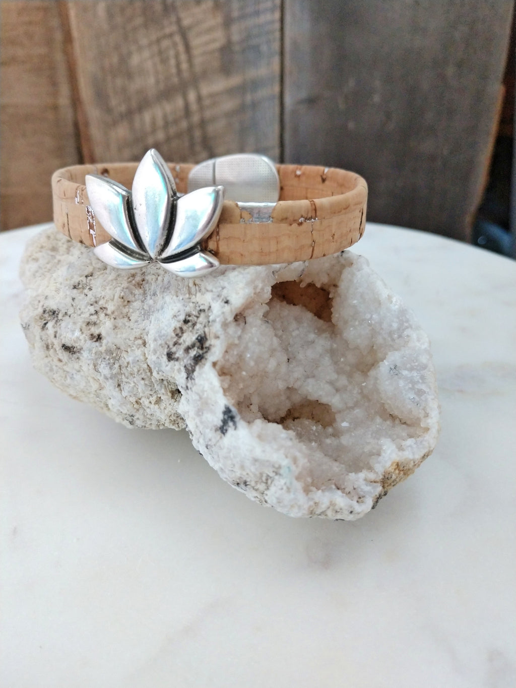 Portuguese natural cork with silver flecks is embellished with a silver lotus flower slider. This comfortable bracelet is secured with a silver magnetic clasp.