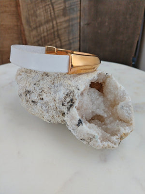 I love the look of this bracelet! White fine Italian leather is attached to a brassy, rose gold half circle magnetic clasp.