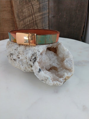 An earthy mix of red, orange, yellow, and green is printed onto fine Italian leather. A brassy rose gold magnetic clasp secures the bracelet.