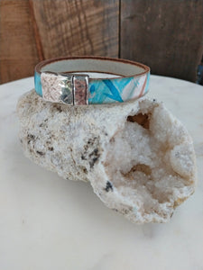 This bracelet features a tie dye-esque print of turquoise and bronze on white fine Italian leather. A textured, rectangle magnetic clasp keeps it secured.