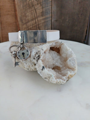 White fine Italian leather holds a silver heart lock and key charms. The bracelet is secured with a magnetic clasp.