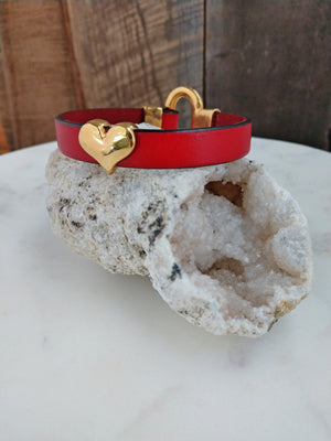 Red fine Italian leather is accented with a shiny, gold heart. The bracelet is secured with a gold horseshoe clasp.
