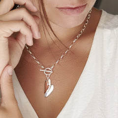 Model wearing 925 sterling silver heart with a second rose gold plated heart necklace (CHN10991)