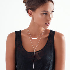 Woman wearing delicate silver Y chain with minimalist vertical bar necklace