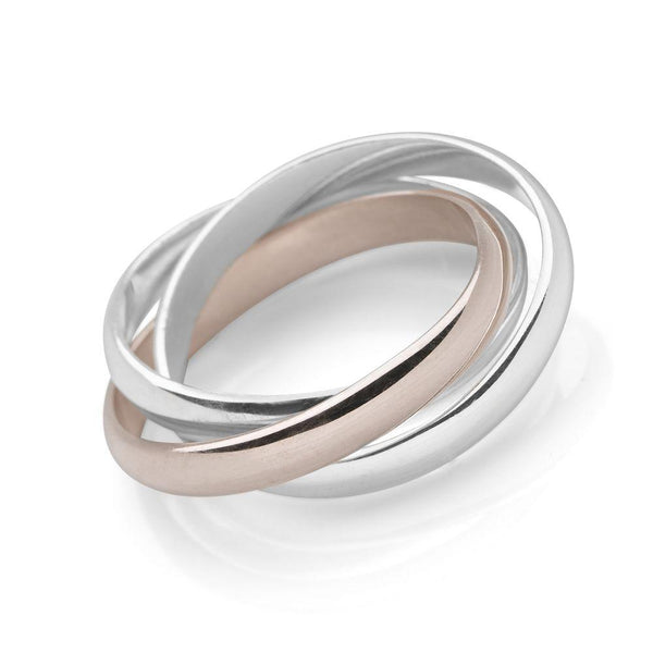 Two interlocking sterling silver bands and a single pale rose gold band ring