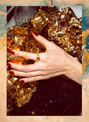 A woman's left hand wearing an 18K gold and cabochon ruby ring titled 'Small Stardust Ruby' from the 1990s made in Denmark by fine jewellery designer Arje Griegst. The wavy band on the ring turns wider at the top where a smooth, shiny cabochon-cut red ruby is embedded in the gold. The surface of the gold isn't smooth but looks coarse, as if the gold resembles the surface of the moon.