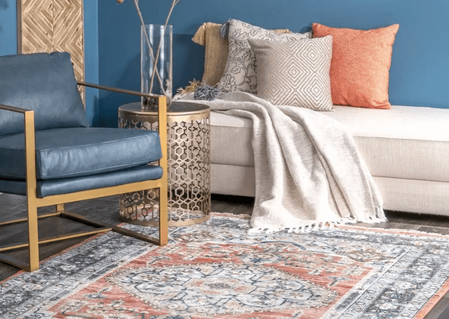 A colorful area rug with matching pillows and chair from Insider.com