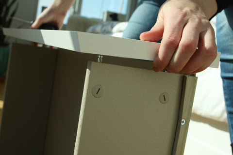 A close up of a person attaching the drawer front to the actual drawer.