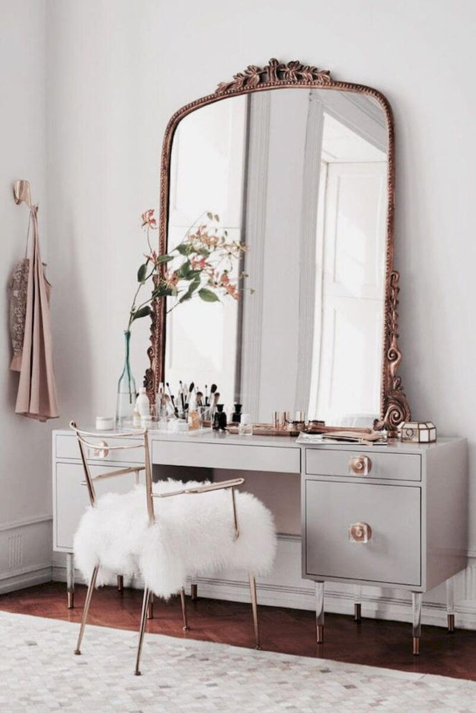 Oversized mirror on a vanity in a bedroom with a neutral color palette.