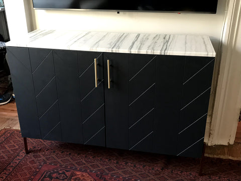 Close up of a Besta cabinet with Eleanor fronts that were painted black. A marble top and brass legs and pulls were added.