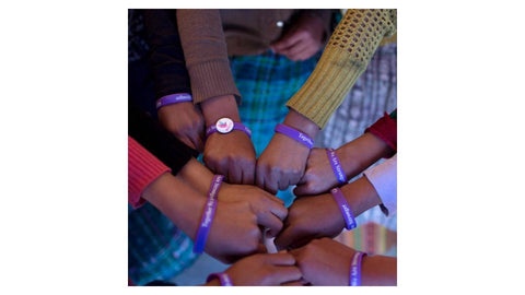 A close up of the arms of a group of girls showing off their Girl Up bracelets
