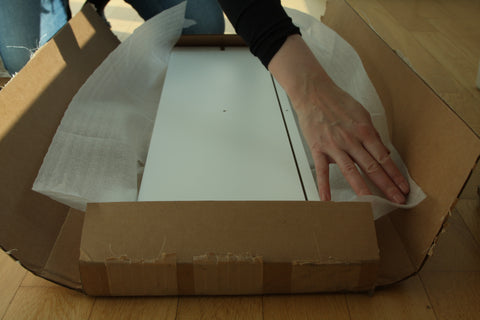A person taking the drawer fronts out of the box.