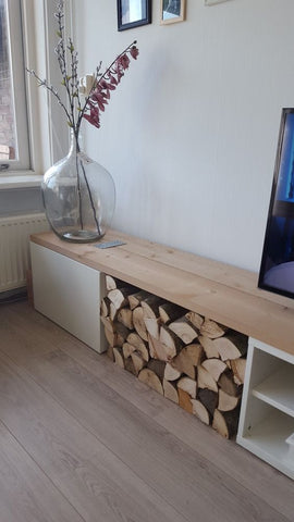An IKEA Besta with an open space that has fire wood being displayed.