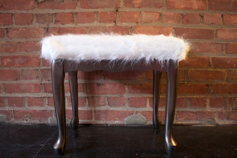 A wooden stool with faux sheepskin