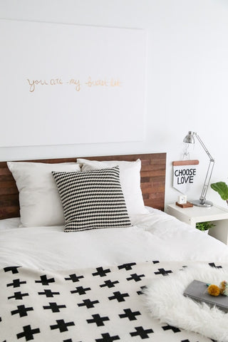 A wooden headboard from IKEA attached to a bed