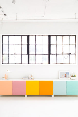 The Besta cabinet running along white kitchen wall. Each cabinet door is painted a different bright color.