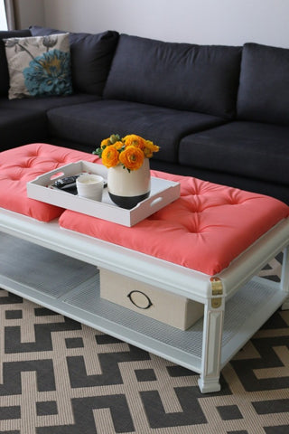 a coffee table painted gray with pink cushions upholstered on top