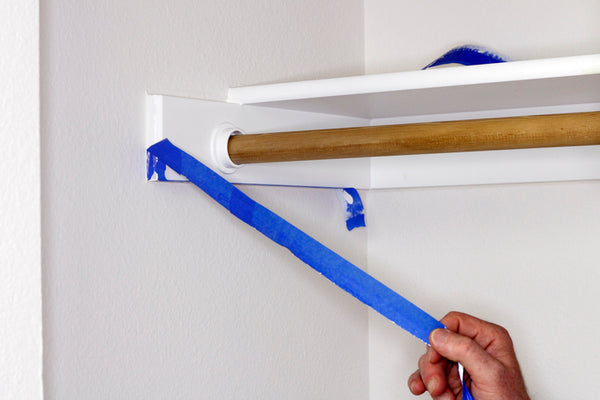 Peeling off blue painter's tape in a closet
