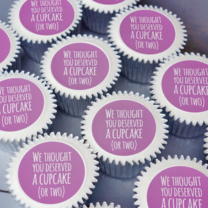 "Cupcakes with edible printed discs saying ""We thought you deserved a cupcake""  in purple"