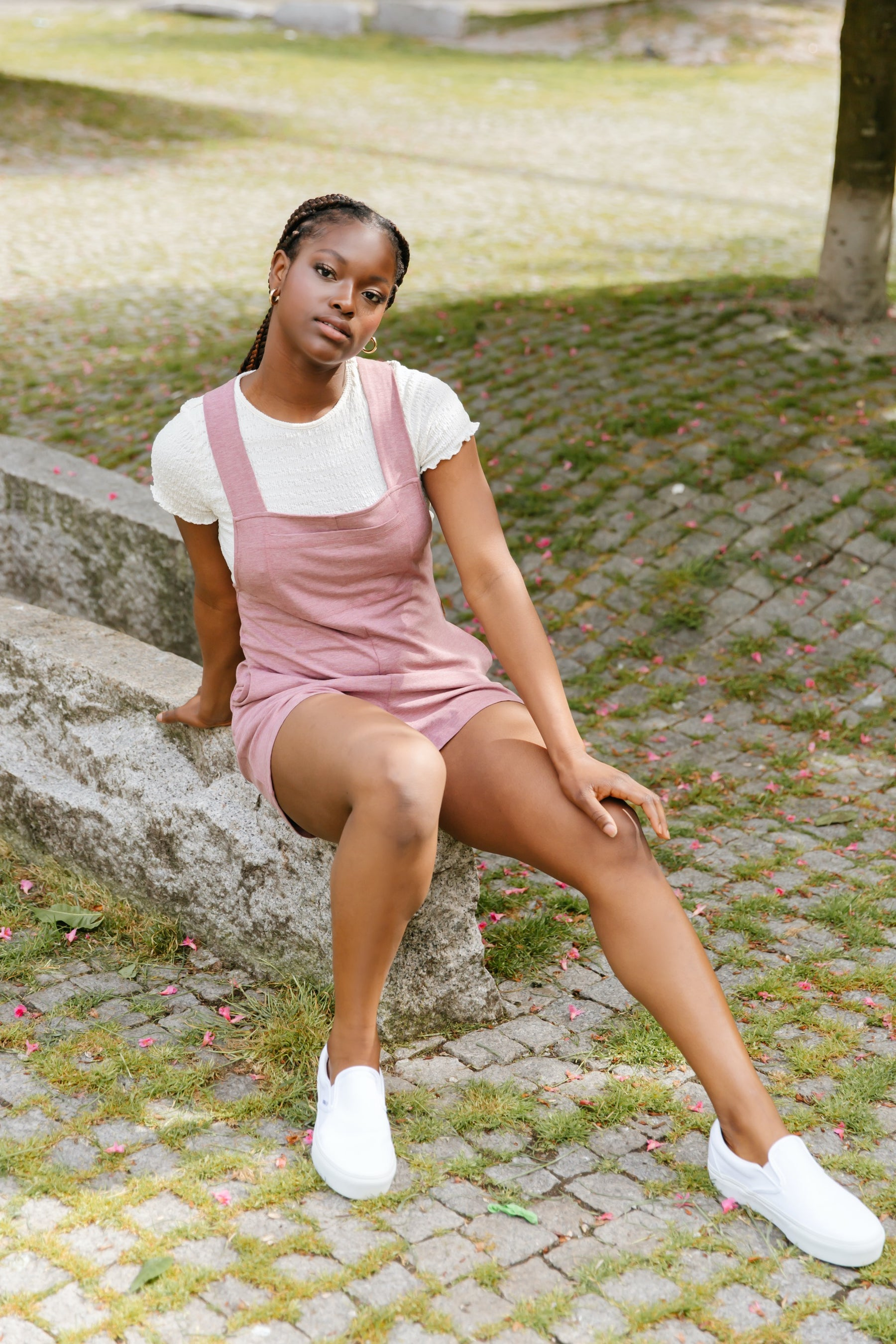 lady wearing pink romperalls with white tee and white sneakers
