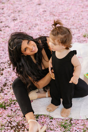 mom and child wearing matching black smash + tess rompers in front of pink blossom