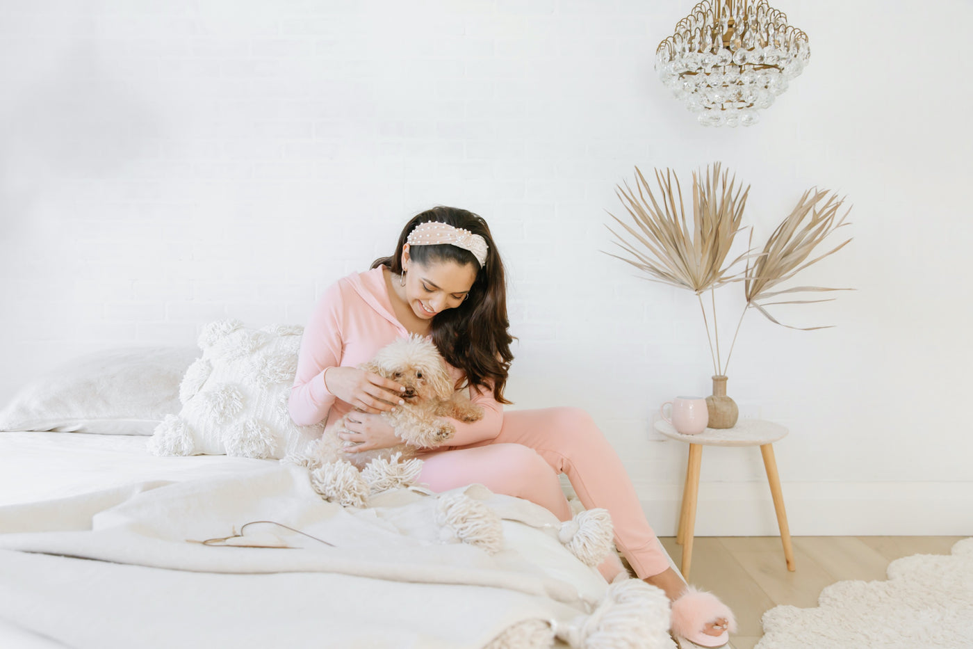 lady wearing pink jillian harris smash + tess romper with dog on bed