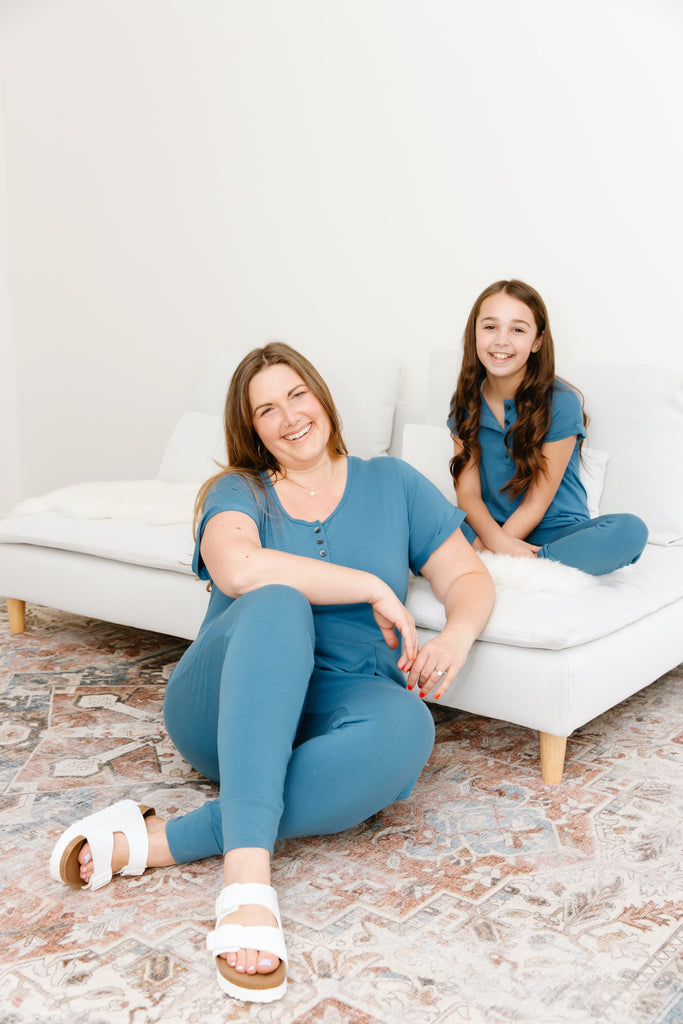 lady and child wearing matching blue smash + tess rompers sat on couch