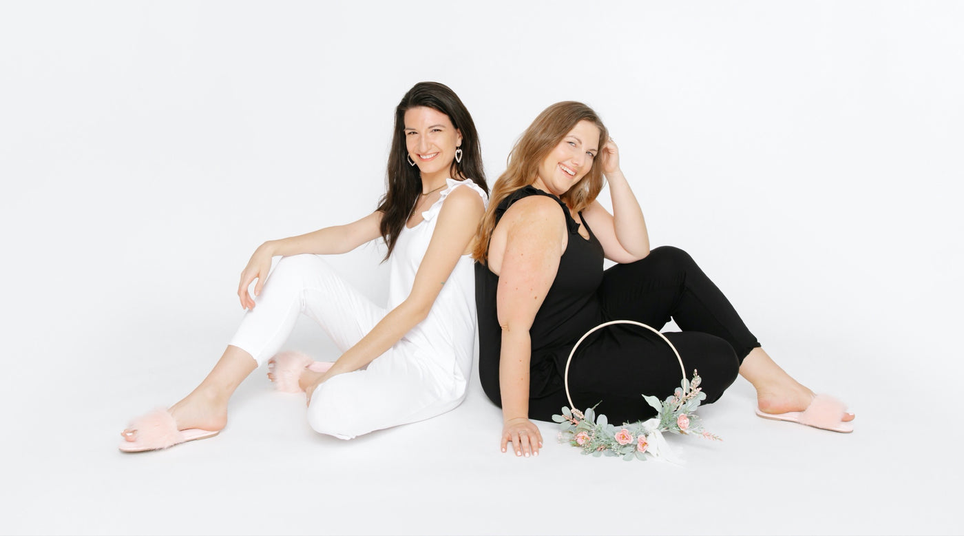 bride and bridesmaid wearing smash + tess bridal rompers in studio with flowers