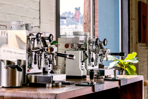 ECM Mechanika V Slim and Rocket Appartamento espresso machines side by side on a wood table, Clive Coffee - Lifestyle