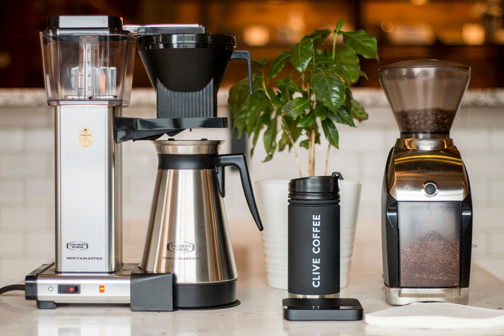 Technivorm Moccamaster coffee maker with thermal carafe in stainless steel on a counter alongside a Baratza Virtuoso coffee grinder, Clive Coffee - Lifestyle