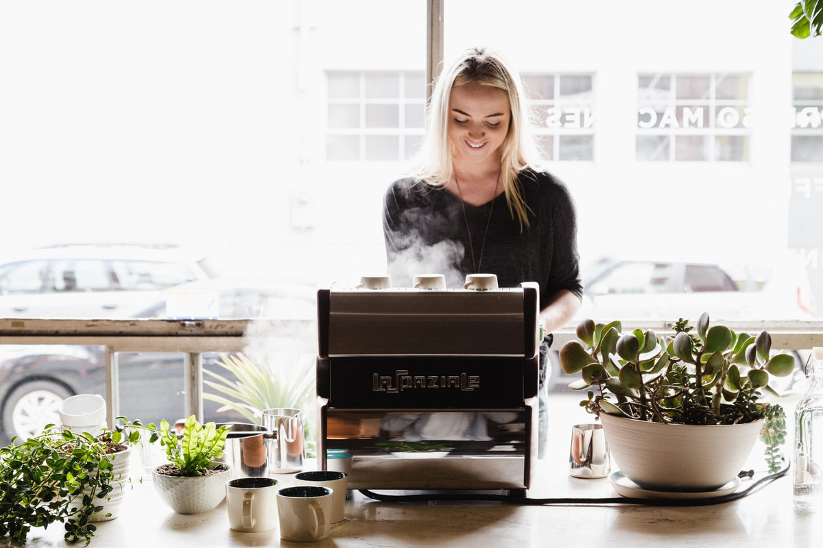 Woman steaming milk on a La Spaziale single group espresso machine, Clive Coffee - Lifestyle