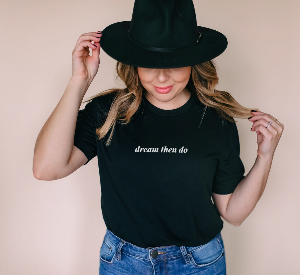 woman wearing black minimalist t-shirt with the phrase dream then do printed on the front