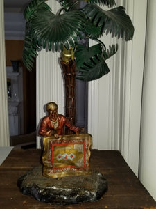 Cold painted bronze lamp of a rug seller with palm trees