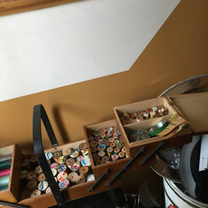 Antique solid wood dovetail sewing kit with 200 rolls of different color threads, 500 needles, tons of pins just to name a few. THIS IS A SEAMSTRESS ORGANIZATIONAL DREAM. THE UNIT FOLD INTO A CARRYING CASE THEN OPEN INTO 3 levels of sewing dream.