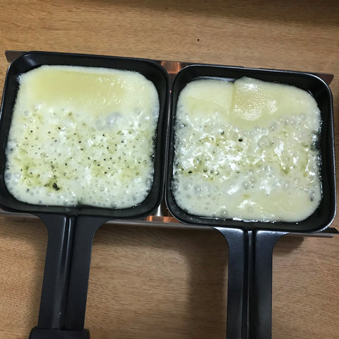 Melted Raclette Cheese in dishes of the Alpine Raclette Melter