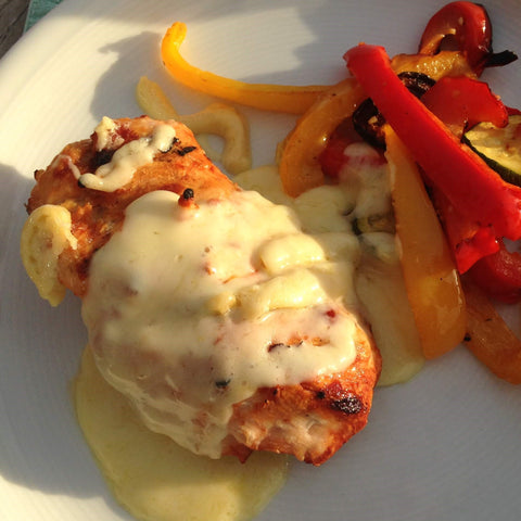Melted Raclette Cheese over grilled chicken breast with roasted peppers and Zucchini